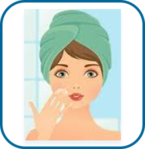 woman washing face in bathroom mirror with towel on head
