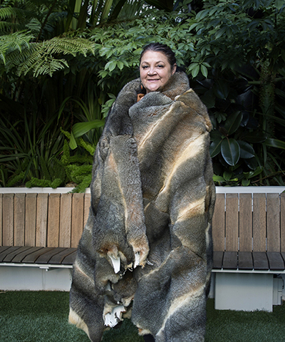 Aboriginal woman and breast cancer survivor Deb wrapped in the finished possum skin cloak