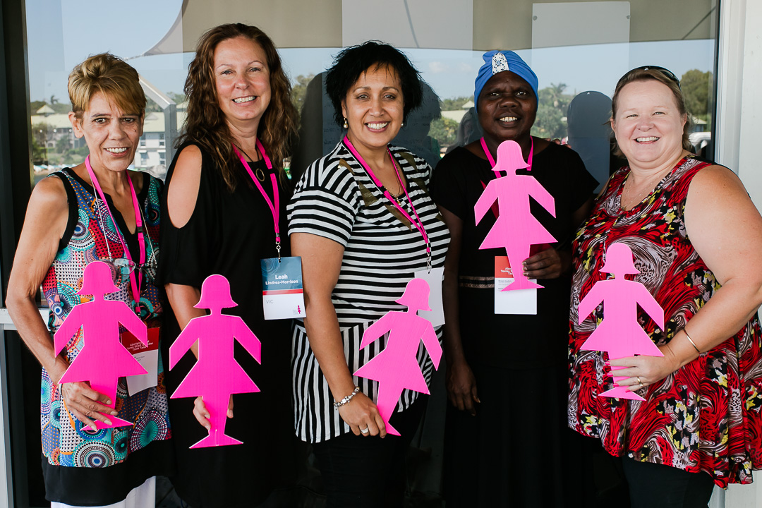 Prof Jacinta Elston with four summit attendees all holding Pink Lady silhouettes