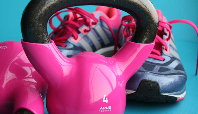 Pink kettle bell near to running shoes with pink laces